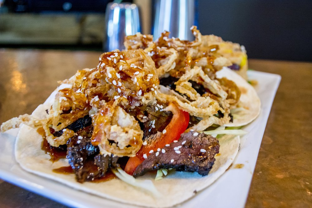 Asian Steak Tacos ($9) with shredded cabbage, bell peppers, fried onions, teriyaki sauce and sesame seeds.