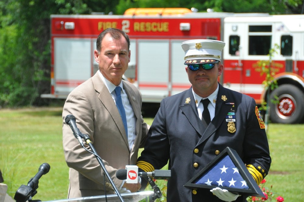 Rep. Tom Suozzi (D-Huntington), left, presents a flag that flew over the Capitol Building to Chief Froehlich.