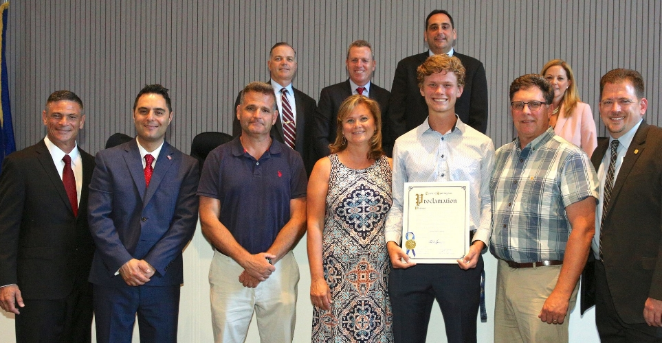 Walt Whitman High School junior Jack Poplawski, third from right, is joined by his parents and South Huntington School District officials at last month's town board meeting, at which he was honored for winning the state championship in the pentathlon.