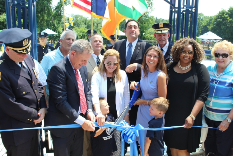 Wife and sons of the late Sgt. Paul Tuozzolo , Lisa, Austin and Joseph, center, are joined by local, state and police officials on Wednesday to cut the ribbon at the new memorial spray park.   (Long Islander News photo/Tatiana Belanich)