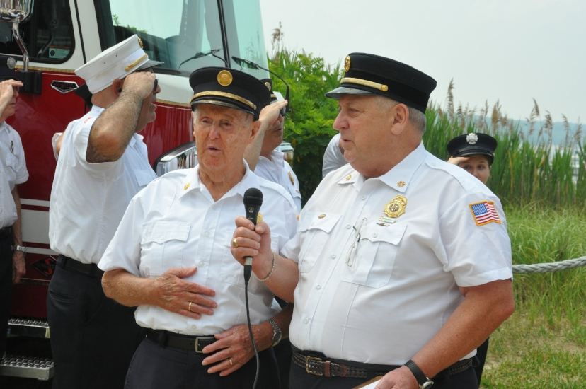 Eaton's Neck firefighter, former fire commissioner and World War II veteran Roy Beach, left, leads the salute to the flag. He turned 92-years-old on July 4.