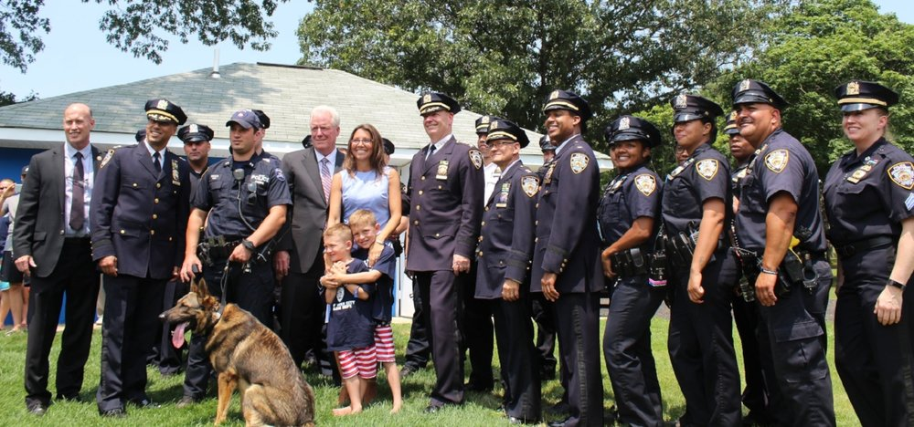Lisa Tuozzolo and sons Austin and Joseph are flanked by members of the Suffolk Police Department.