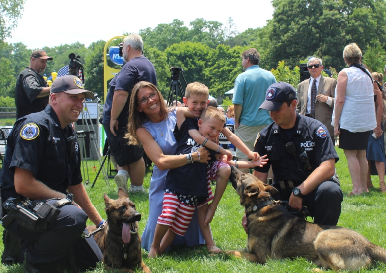 Lisa Tuozzolo and sons Austin and Joseph with officers Schondebare, left, and Bosco, right, of the MTA Police Department Police Canine Unit and their canine officers, Zolo, left-center, and Tuz, right-center.