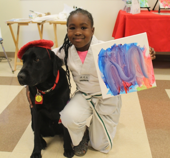 Allison McKenzie, 7, poses with DogVinci, the dog who paints, at Elwood Public Library this past Saturday.   (Long Islander News photo/Tatiana Belanich)