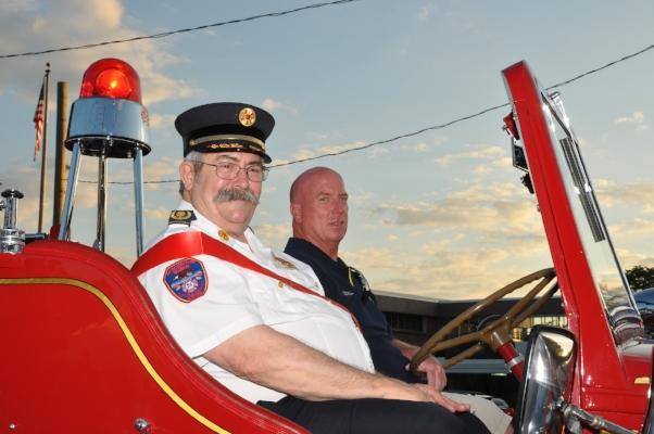 This year's parade grand marshal was Huntington Manor ex-Chief Steve Lygren, left, who has 31 years of service. He rides in the department's antique truck with firefighter Tommy O'Donnell, right.   (Photos by Steve Silverman)