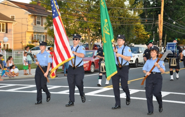 The Greenlawn Fire Department Color Guard marches.