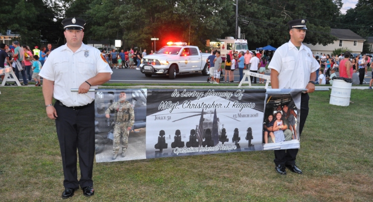 Members of the Commack Fire Department carry a banner in memory of Master Sgt. and Honorary Chief Christopher Raguso, who was killed earlier this year in a helicopter crash in Iraq.