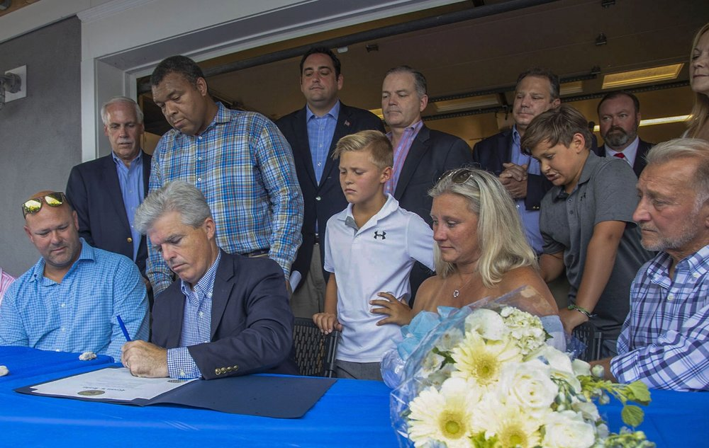 The Weiss Family joined state, county and town officials Tuesday as County Executive Steve Bellone signed Ryan's Law.   Photo/Suffolk County Legislator William Spencer's Office.