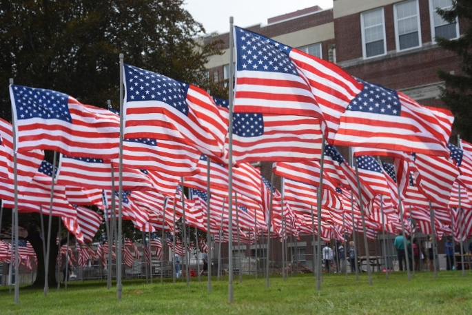 Hundred of American flags, each dedicated to a veteran or active military service member, fly in the Field of Honor in front of Huntington Town Hall.