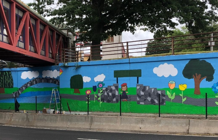 A mural painted by students at Birchwood Intermediate School brightens the LIRR underpass in Huntington Station. The mural has gotten tons of positive feedback from the community, showing the children that what they are doing matters.