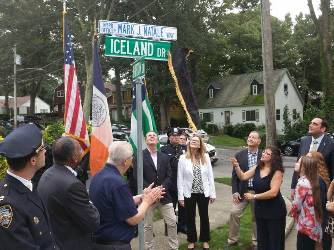 Mayra Natale unveils a street sign dedicating Iceland Drive to honoring the memory of her late husband, Mark.