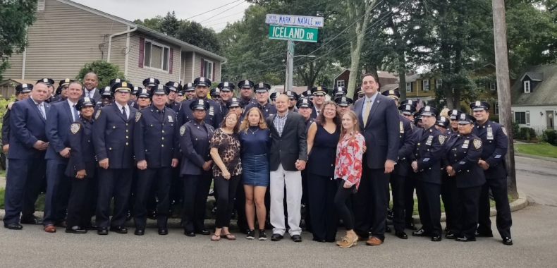 94th Precinct officers with NYPD First Deputy Commissioner Benjamin B. Tucker stand with the Natale family in front of the sign dedicating Iceland Drive in honor of NYPD Officer Mark Natale.