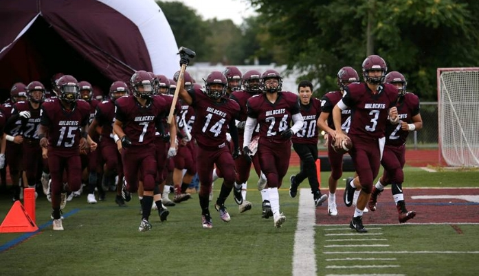 Senior quarterback Quinn O'Hara (No. 3) leads the Walt Whitman football team onto the field before their 35-24 win over Sachem North.