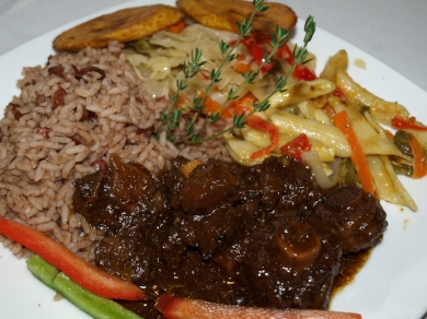 Oxtail Dinner ($15.50/medium, $18/large) served with a side of vegetables, fried plantains, rice and Rasta Pasta.