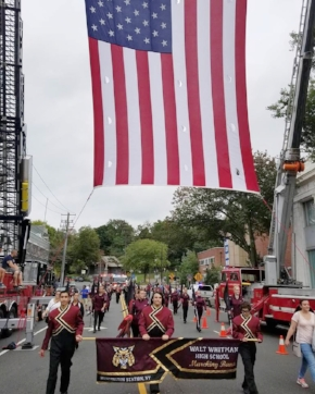 Walt Whitman High School marching band passes under the American flag during Sunday's Long Island Columbus Day Parade in Huntington.  Photo/South Huntington School District