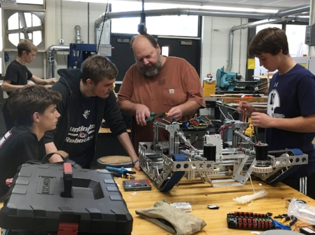 Mentor, Donald Fisher works with Huntington High School students, Anthony Amitrano, Nick Bozsnyak and Patrick Langton to build a robot.