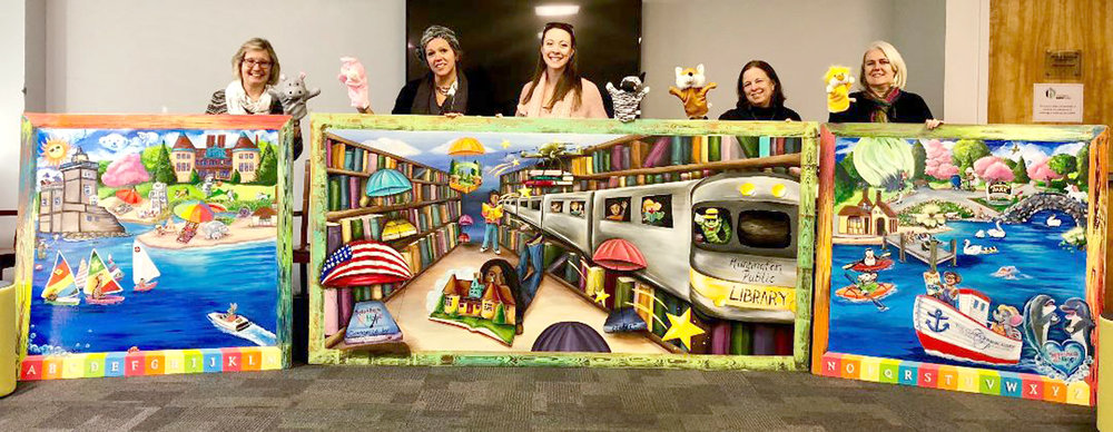 Library Director Joanne Adam, Founder of Splashes of Hope Heather Buggee, artist Tiffany Bedell, Branch Manager Mary Kelly, and Librarian for Youth and Parent Services Corinna Jaudes display murals created by Splashes for new rooms at the library..