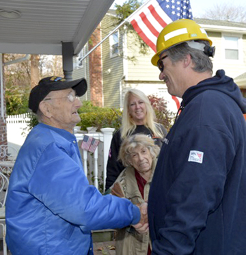 Morris Koffer thanks PSEG Long Island employee Frank Moorhus who organized volunteers to do yard work on the 96-year-old WWII veteran's property.  PSEG photo