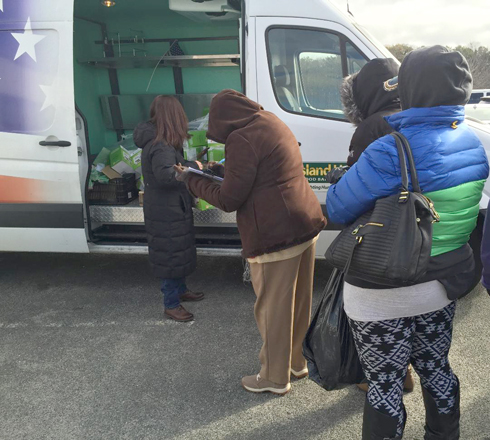 An Island Harvest mobile pantry distributes food to those in need. The non-profit has stepped up its outreach to help workers who are missing paychecks as a result of the government shutdown.  Photo/Island Harvest