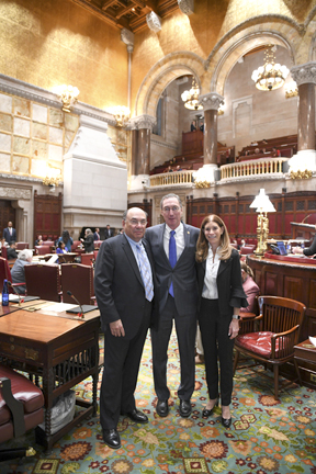Dix Hills residents Linda Beigel Schulman, right, and Michael Schulman, left, join Senator Jim Gaughran on the floor of the State Senate for passing of gun control legislation.