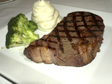 Rib Eye Steak is served simply — with mashed potatoes and broccoli.