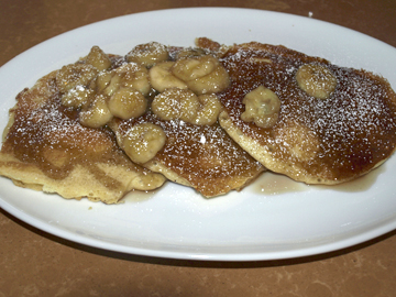 La Piazza's thick and fluffy pancakes are topped with bananas and powdered sugar