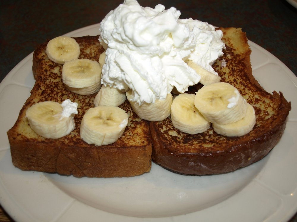 Challah bread French toast is topped with banas and whipped cream.