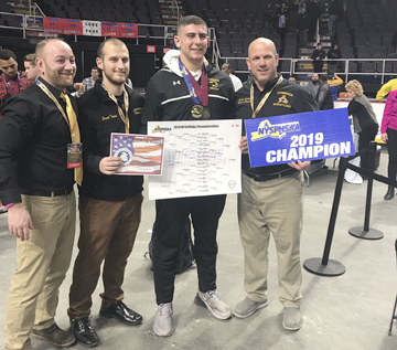 Commack senior Joey Slackman, second from right, celebrates with his coaches after winning the 285-pound state championship on Feb. 23.