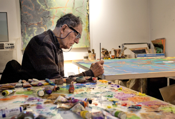 Stan Brodsky signs one of his paintings in his Huntington studio in one of many photographs by Peter Scheer that document the artist and his work.  Photo/Peter Scheer