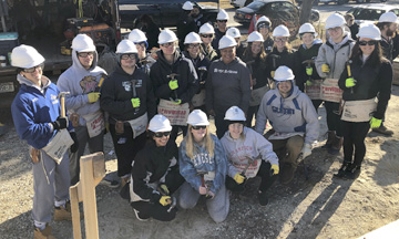 Habitat for Humanity of Suffolk executive director and John Glenn alumnus Tracey Edwards joins Glenn students who were helping to raise the walls of a Habitat for Humanity home on March 13.  Photo courtesy   Habitat for Humanity