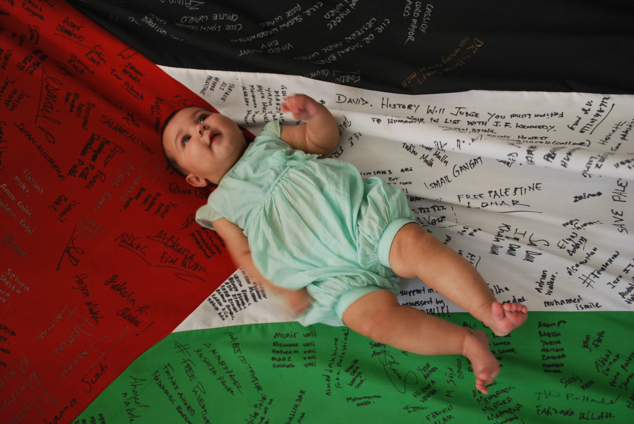 Haniya Aqsa Afzal laying on the Palestine Peace Flag