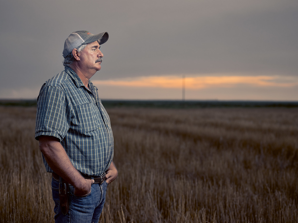 farmer standing in his field during a sunset
