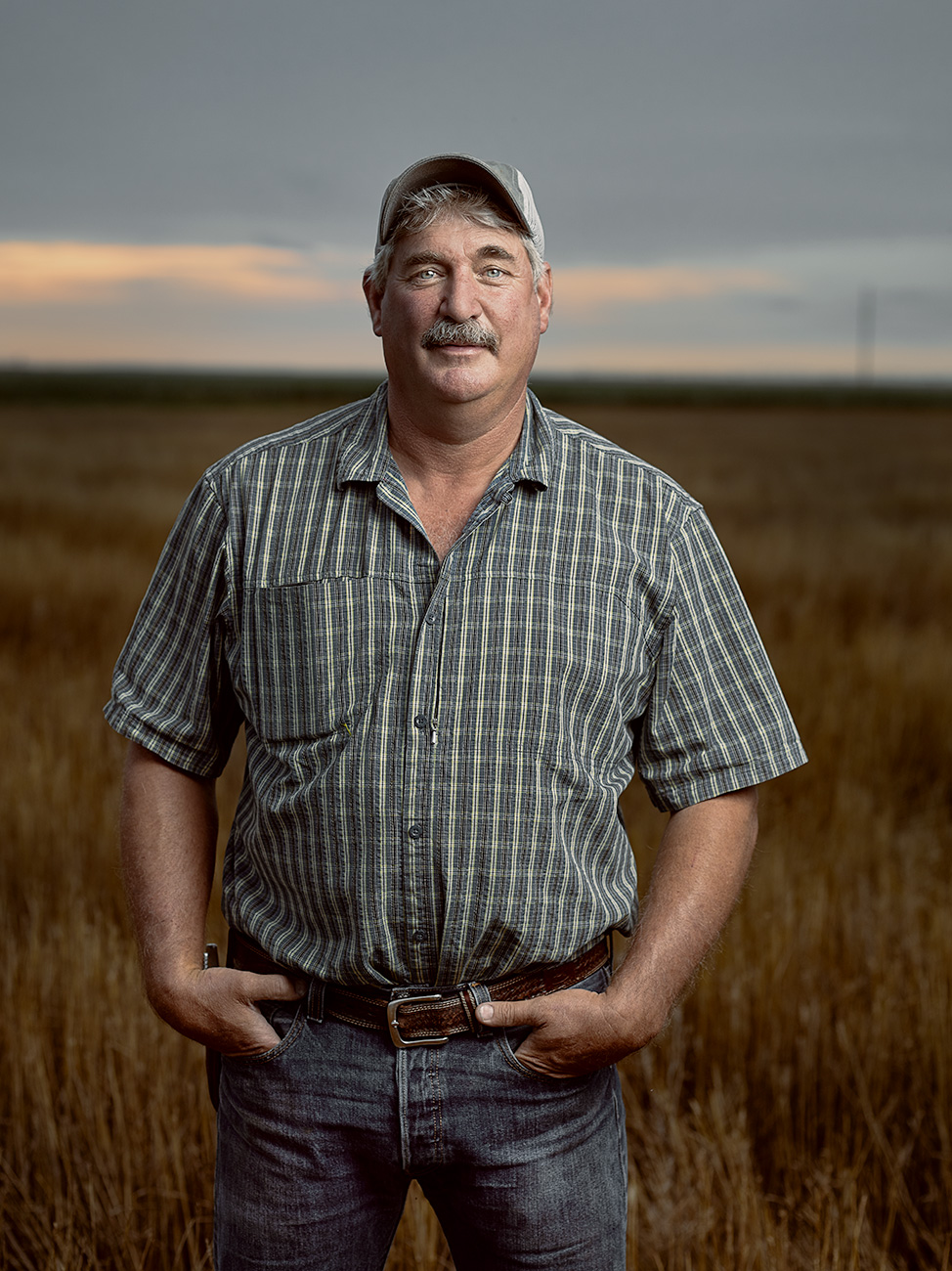 A photo of a farmer standing in a harvested field