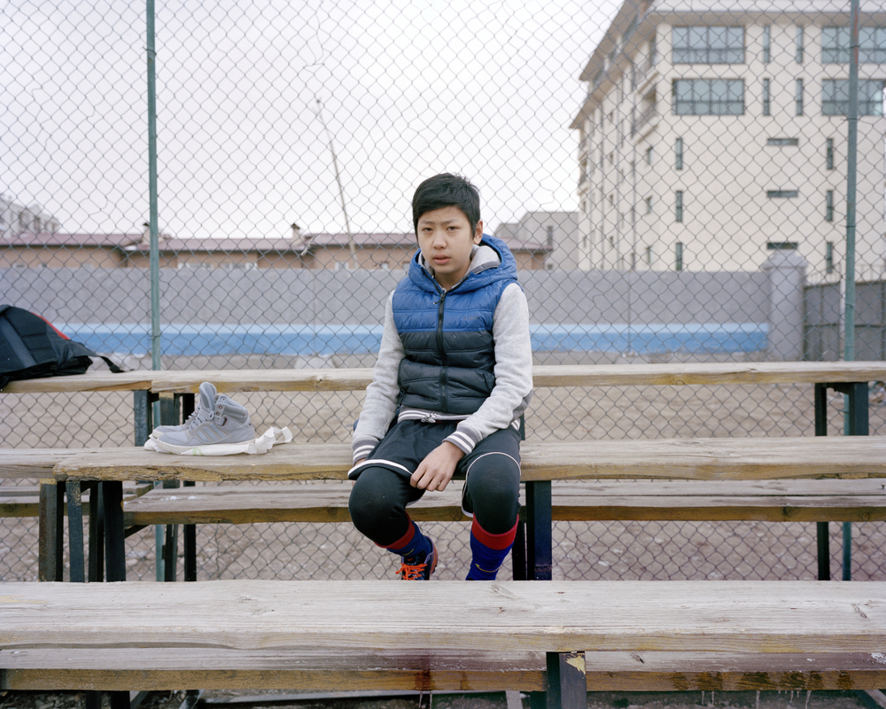 A Deren Under 13's Academy player, sits on the bleachers before training at the Deren training pitch, Ulaanbaatar. April 2014.  FC Deren are allowed to use the miniature pitch that joins the MFF stadium to train their children as they are named after the construction company that built the stadium. There is a huge shortage of facilities for the development and training of football in Mongolia.