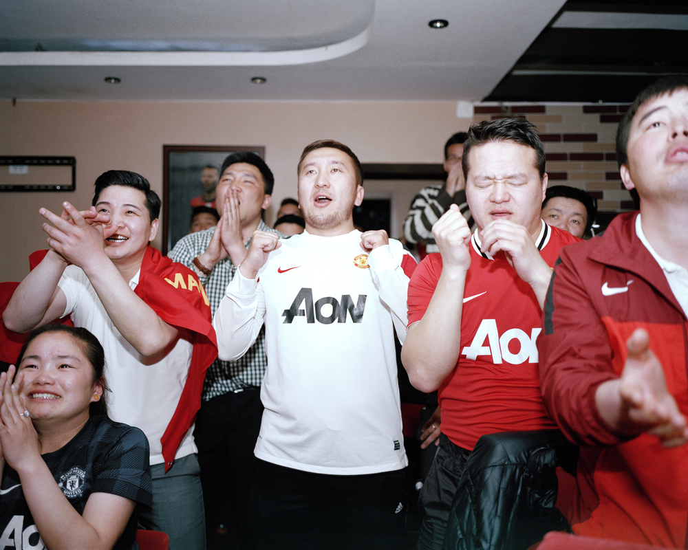 Supporters watch Manchester United Vs Bayern Munich at an illegal broadcast of the match at the Manchester Pub, Ulaanbaatar. April 2014.  Due to the high levels of Alcoholism in the adult population in Mongolia, all bars are ordered to close at midnight. Because of the 7 hour time difference, many matches begin as late as 3am in Mongolia. This does not deter the fans in the slightest, such is the support the bars experience their heaviest trade after hours, with packed venues showing the game.