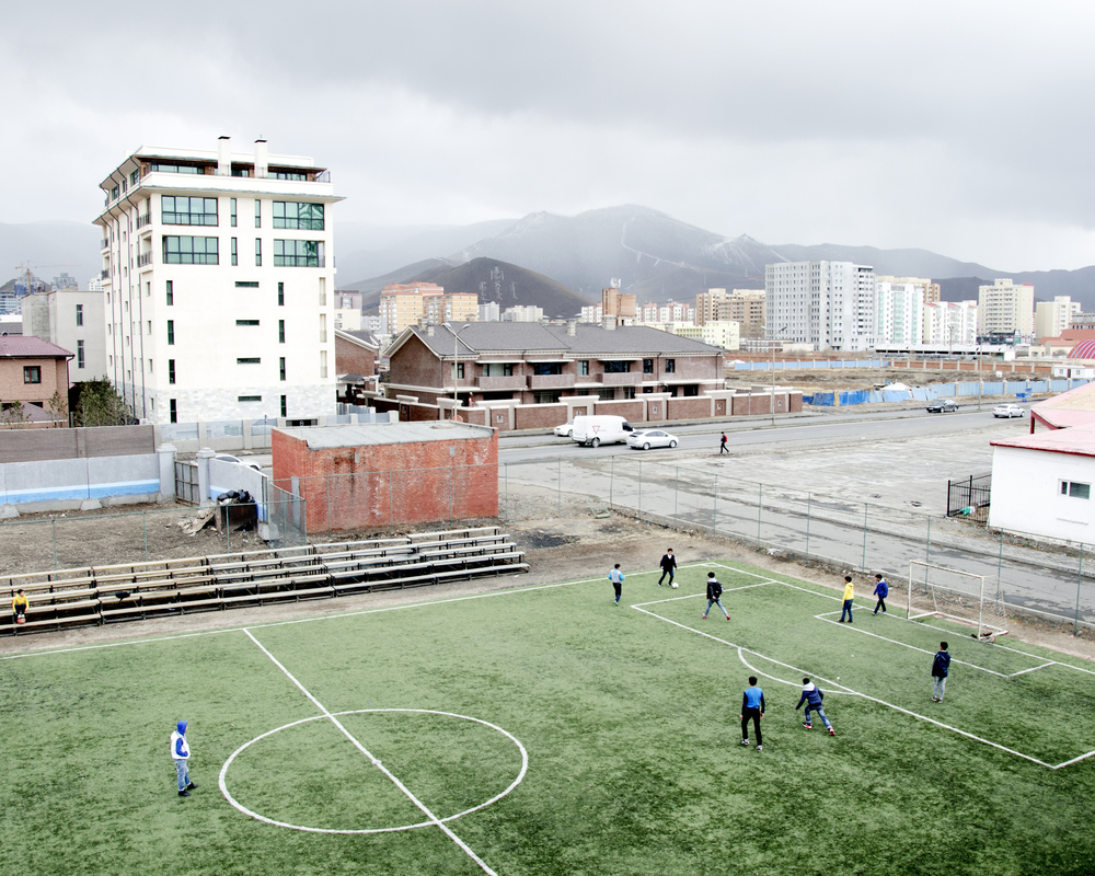 The dramatic landscape of Mongolia surrounds the city of Ulaanbaatar. Snow clouds loom over the children playing football on a miniature artificial pitch as the extreme cold temperatures of winter in Mongolia have finally subsided, football season is ready to begin. April, 2014.