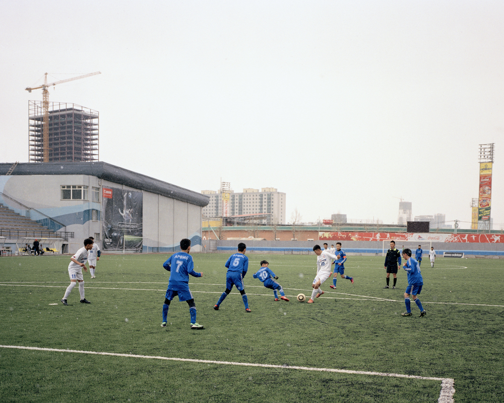 FC Deren and FC Ulaanbaatar University compete in the under-17 national championships in the snow at the MFF Stadium, Ulaanbaatar, April 2014.  FC Deren, named after the Dutch construction company that built the stadium, are the only academy in the country that train children and develop them together from the ages of 10 – 17. Many of the Deren players go on to play for teams in the Official league of Mongolia, the MFF's Niislel League.
