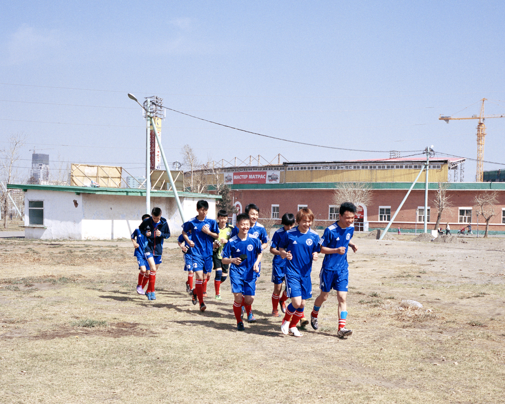 FC Ulaanbaataar University Under 17's warm up before their match, Ulaanbaatar, April 2014.  With the MFF Stadium running fixtures back to back, there is nowhere for the teams to warm up before their game. FC UBU resort to warming up in the dirt in front of the stadium.