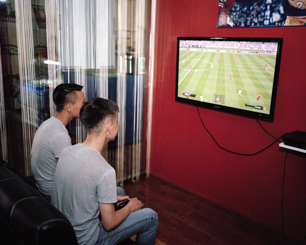 Ochiroo and Buyna, two of the youngest members of Bayangol FC relax by playing FIFA 14 at a gaming cafe, Ulaanbaatar, April 2014.  Mongolia does not feature on any football based game. Despite FIFA 14 containing over 16,000 players, not one is Mongolian.