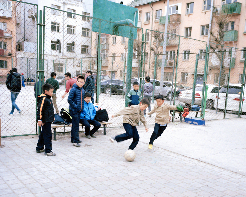 Surrounded by the apartment blocks left behind from the Soviet-era, School children play football in a central park, Ulaanbaatar, April 2014.  Although many have a fierce passion to play football at a young age, the lack of facilities and coaches mean that the children's talent can not be developed. Many choose instead to play basketball as they grow older as it is far more accessible to play.