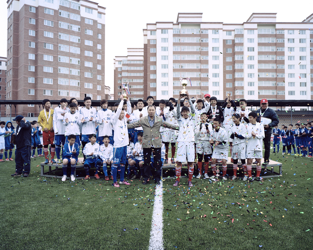 The Under 15 and Under 17 National Champions lift their trophies during the championship ceremony at the MFF Stadium, Ulaanbaatar, April 2014. These players are the first generation that will experience the changing philosophy of Mongolian football, with more belief than ever in the dream of professional football that will change their lives.