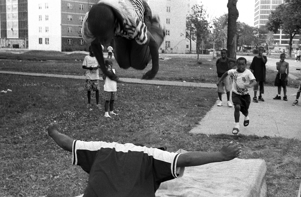 Children at Stateway compete with one another, doing flips on to a discarded mattress.   PHOTO BY PATRICIA EVANS
