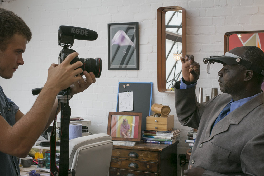 Dan Odida inspecting the Fairtrade Gold hallmark on an earring