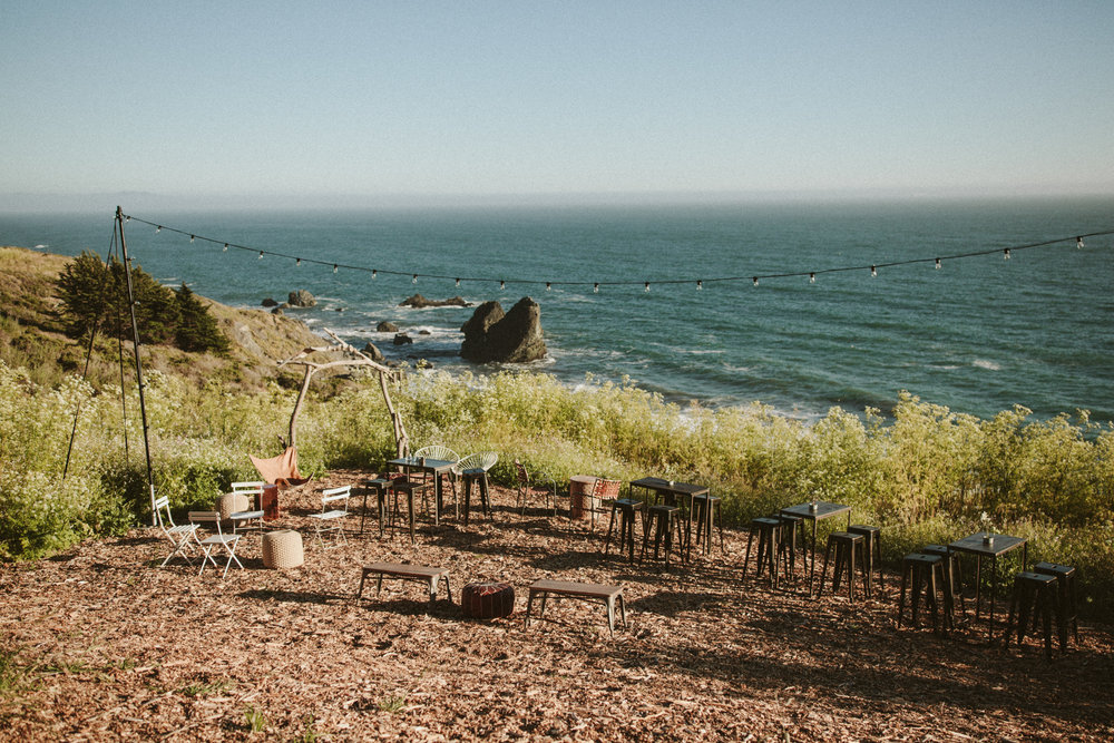 outdoor wedding reception with an ocean backdrop and bistro lights - slide ranch, california
