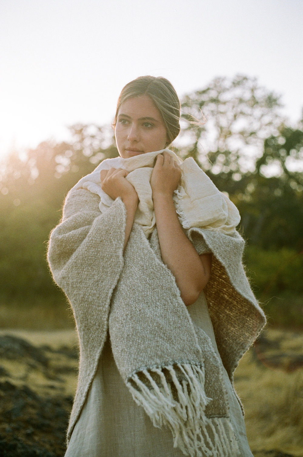 girl in a grass field in a poncho, fashion photography, handwoven clothing woven wares victoria bc