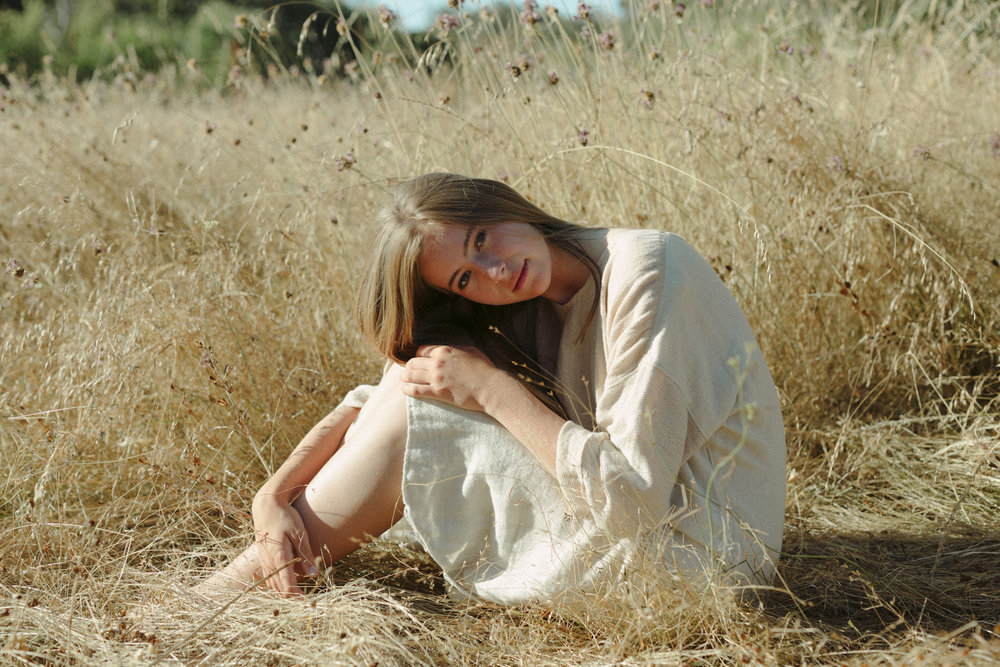 girl in a grass field, handwoven clothing woven wares