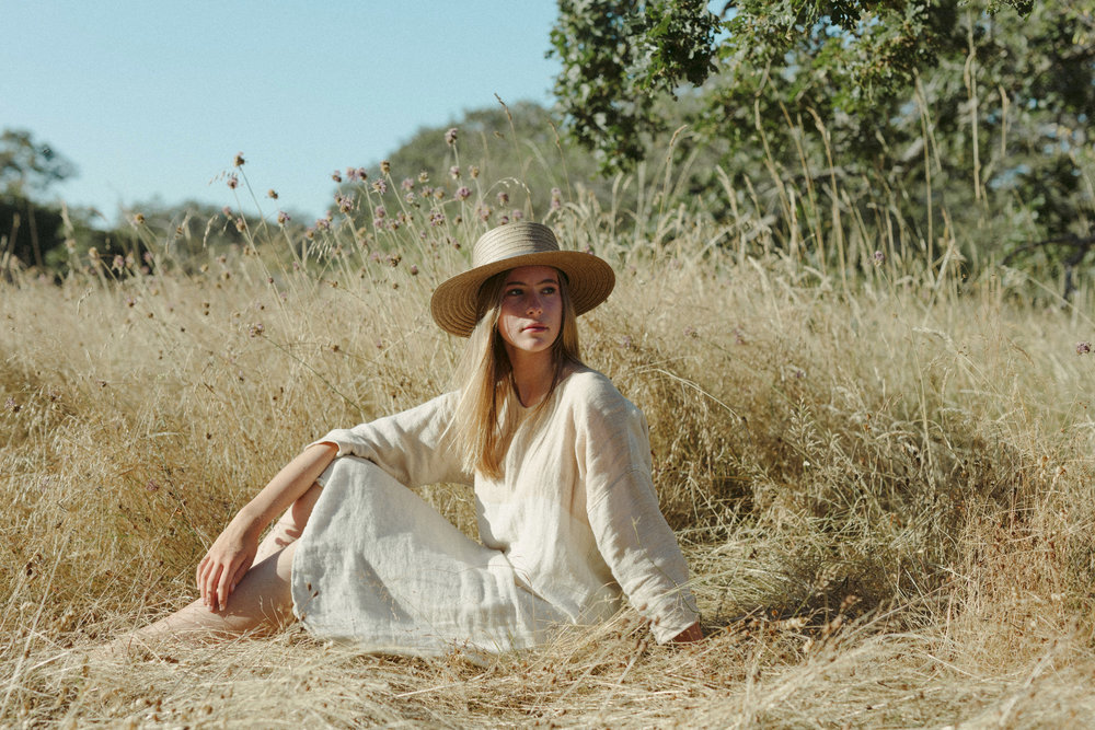 girl in a grass field with a straw hat, handwoven clothing woven wares