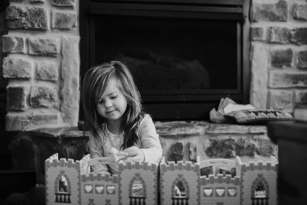 Christmas 2016 | Hannahill Photography | Branson, MO | Documentary Family Photography | a black and white portrait of my niece playing with her toys