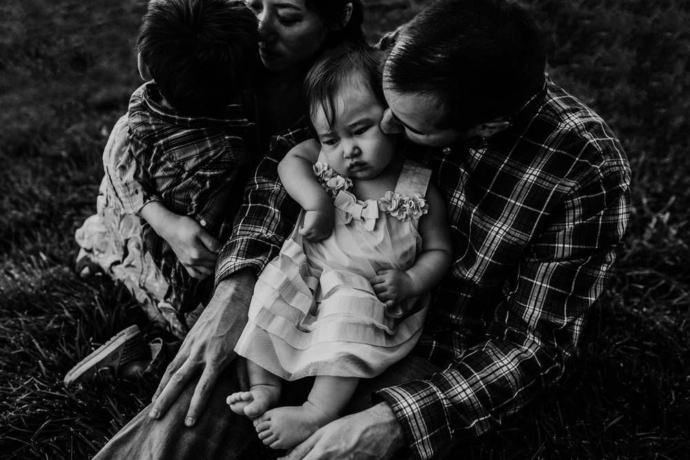 A family sits at sunset with their little girl being adorable | English Landing Park | Family photographer based in Raleigh Durham North Carolina |The Baskett Family Sunset Session | Hanna Hill Photography | Kansas City, MO