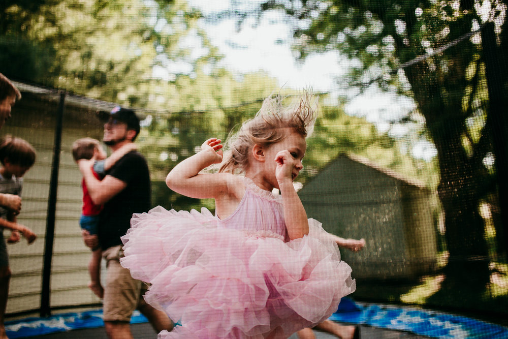 The only little girl in the family jumps to her hearts content on the trampoline in her favorite pink tutu.  The Carter Family : Summer in the Backyard | Hannahill Photography | Kansas City, MO | Family photography lifestyle photographer | Wedding photographer Durham North Carolina Raleigh | Birth photographer Documentary